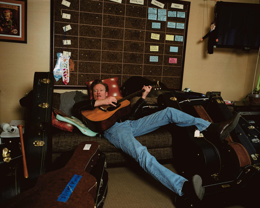 Conan in his Rockefeller Center office, not long before taping the final episode of Late Night playing one of many guitars. This is Conan's favorite way to relax before the show.