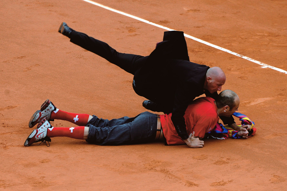 A spectator who accosted Roger Federer is brought down by security staff during the men's final of the 2009 French Open tennis tournament at Roland Garros in Paris, France.