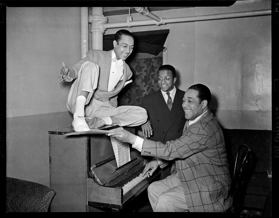 """Duke Ellington at piano, with dancer Honey Coles and Billy Strayhorn looking on, in the Stanley Theatre"" by Teenie Harris © 2006 Carnegie Museum of Art, Pittsburgh"